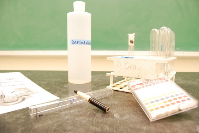 Test tubes in holder, bottle of clear solution and china marker.